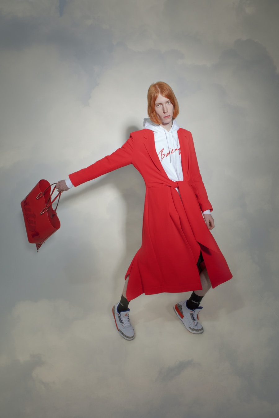 Model wearing a red coat in front of a cloud background