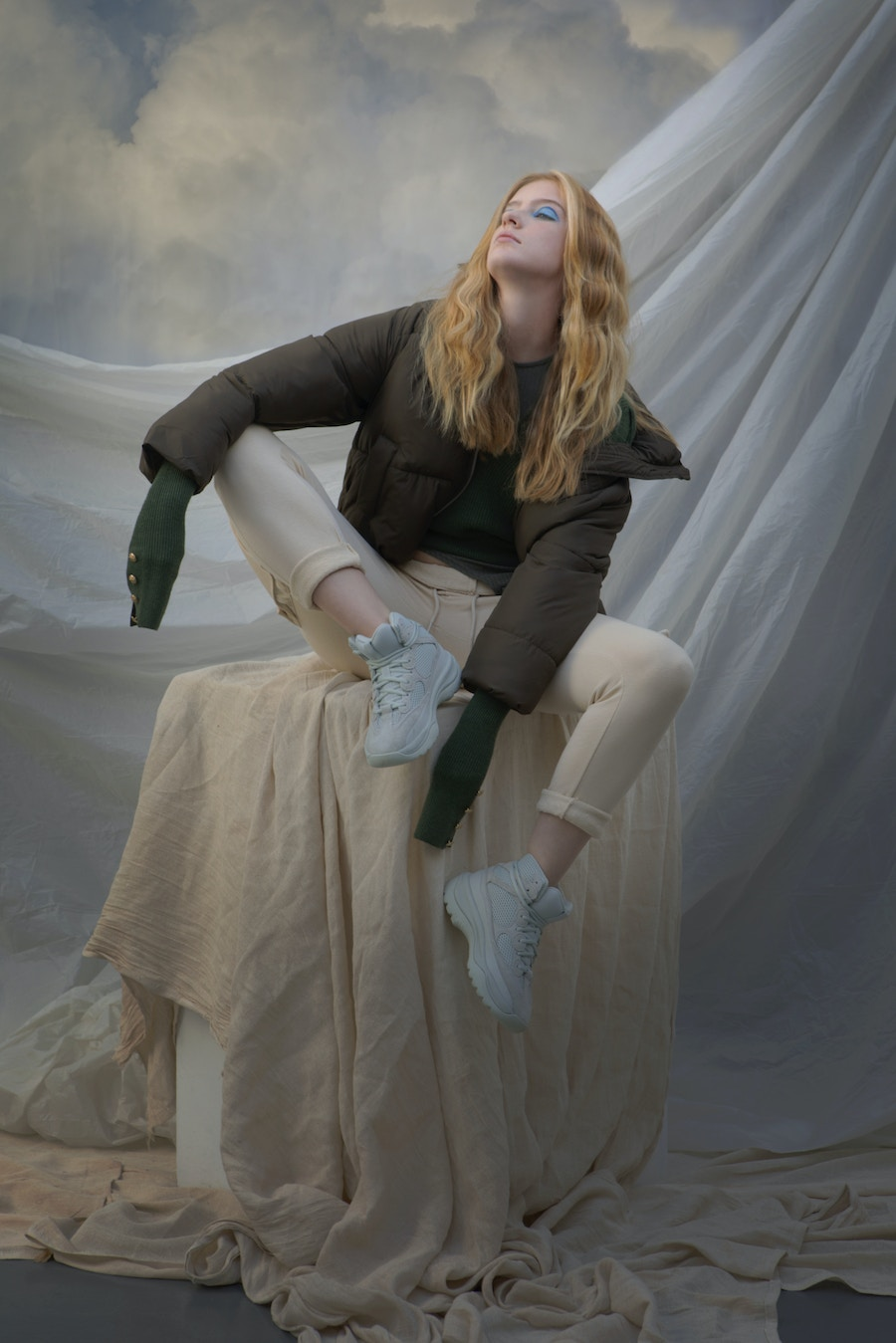 A model sitting on a cloth covered pedestal in front of a cloud background