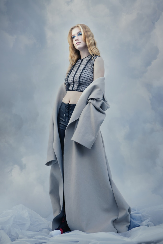 A model standing in front of a cloud background