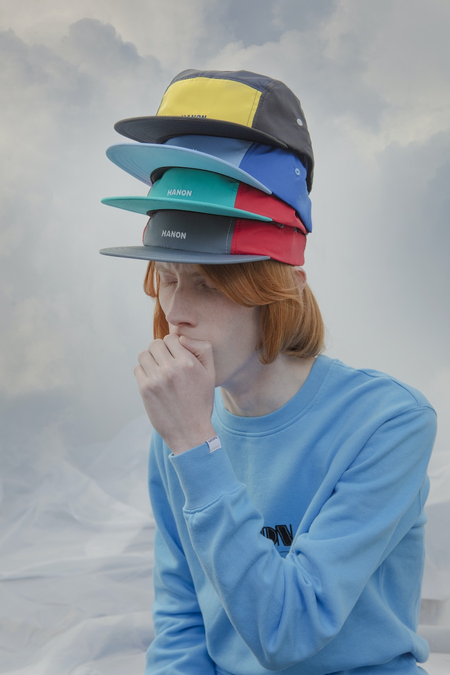 A model wearing four different coloured baseball caps on his head