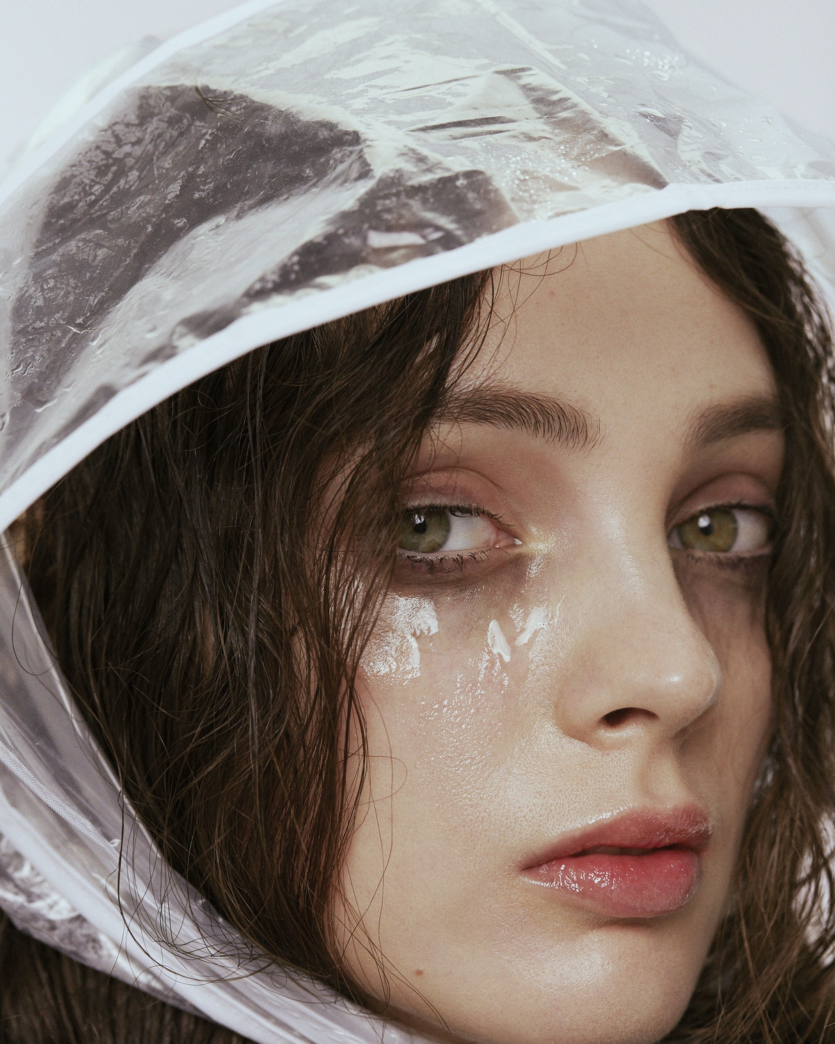 A woman wearing a clear plastic rain hood. Her eyes look watery