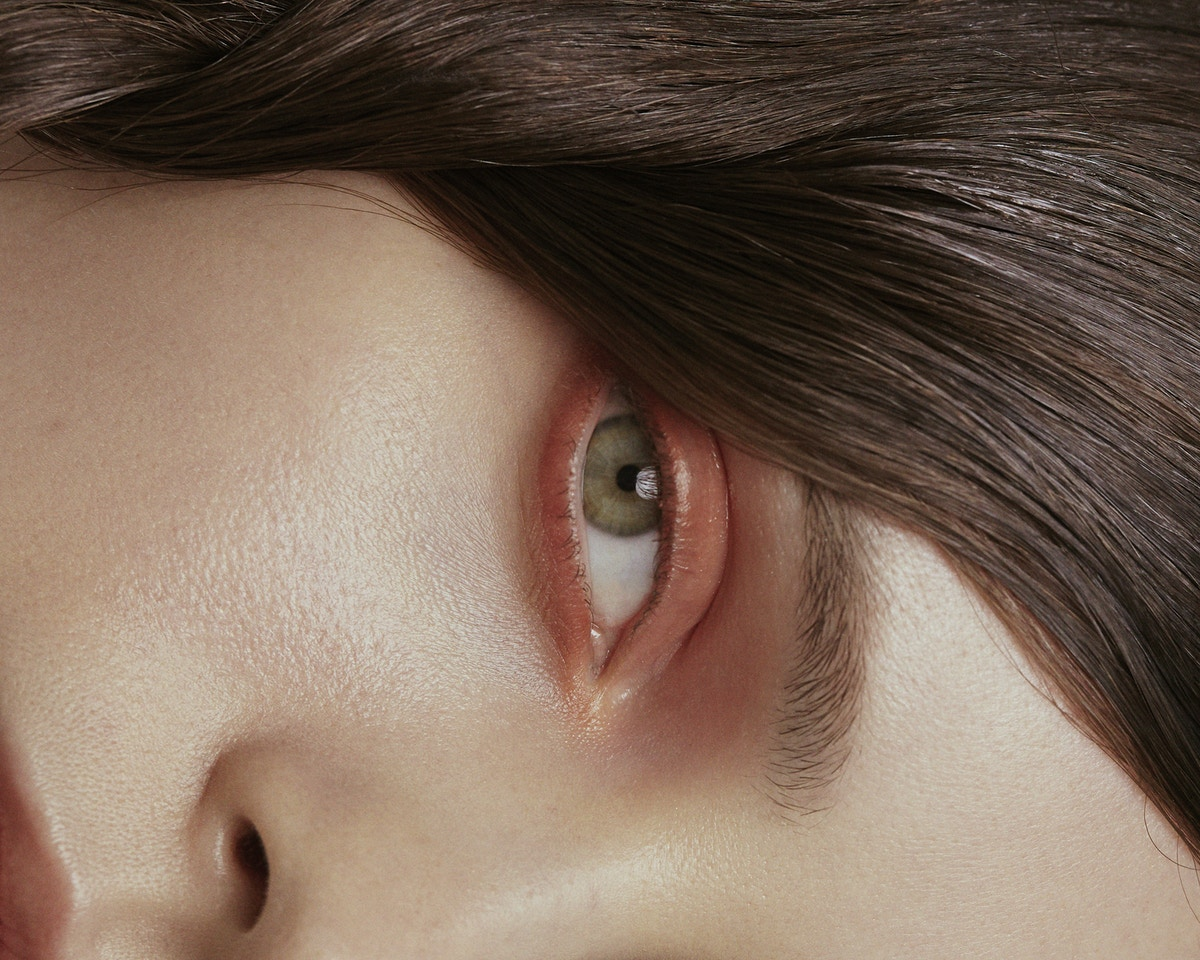 A side view of a woman's eye with pinky-red eye shadow