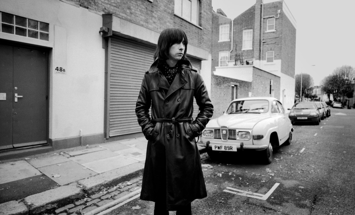 Bobby Gillespie standing on a road dressed in a leather trench coat.
