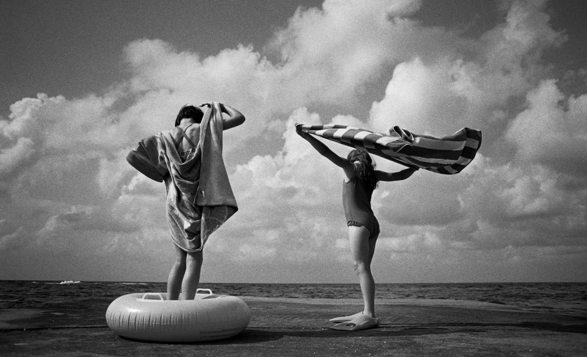 Two girls standing with towels on a beach.