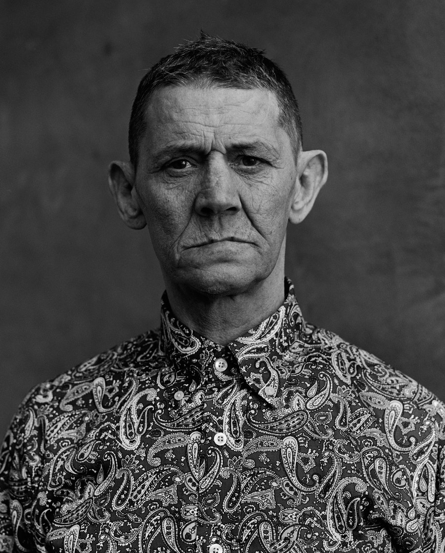 A man dressed in a patterned shirt stares at the camera.