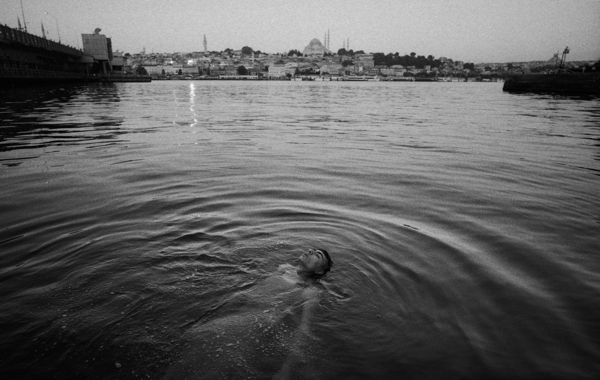 A man swimming on his back with the skyline of Istanbul behind him.