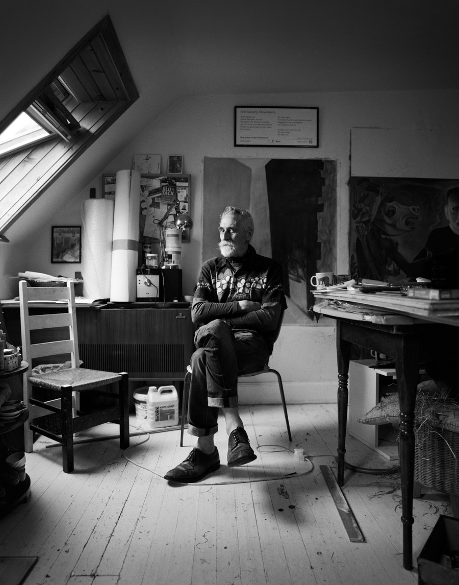 The artist John Byrne sitting with one leg crossed over the other. The room appears to be his studio.