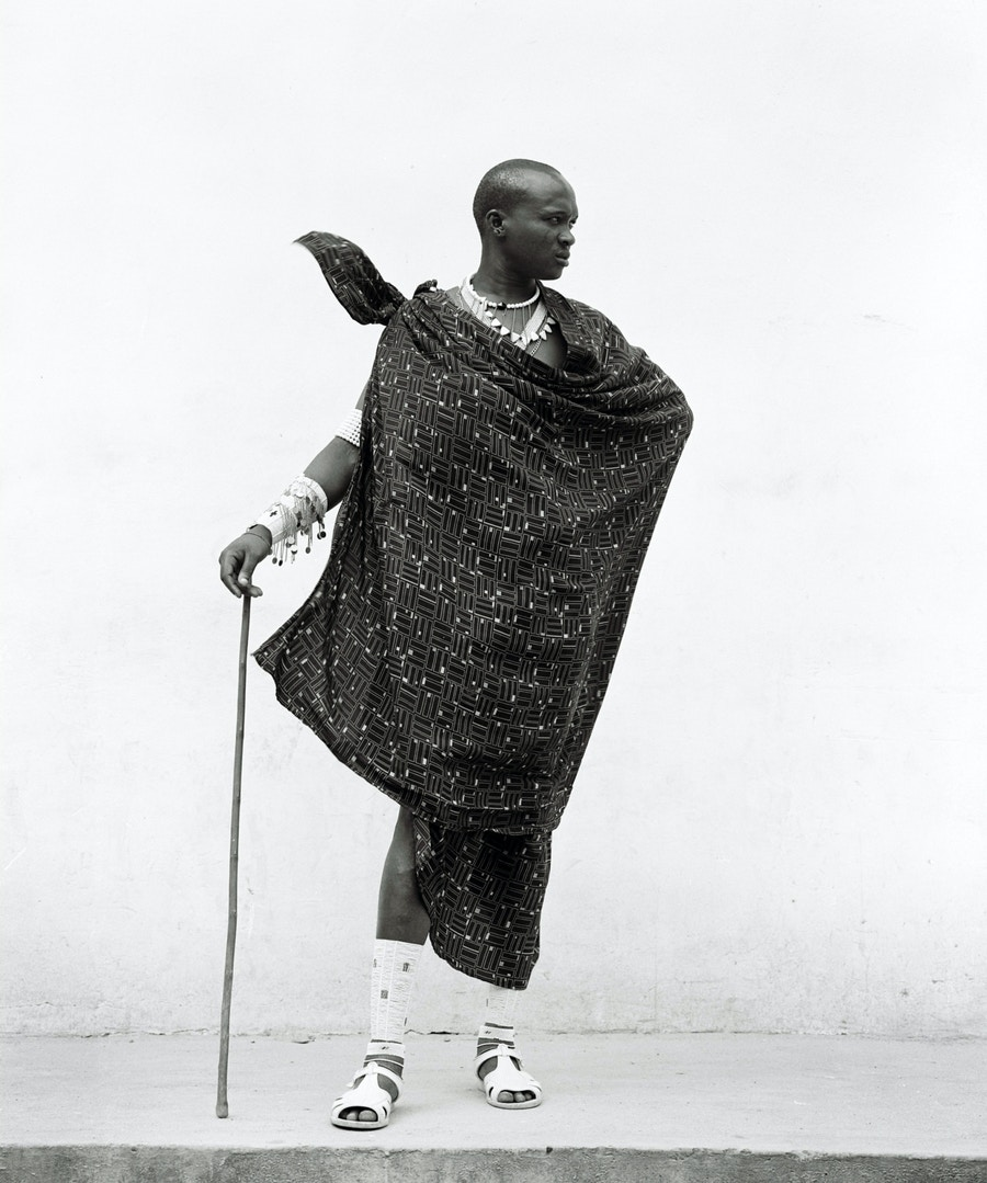 A Massai man standing in front of a white coloured wall.