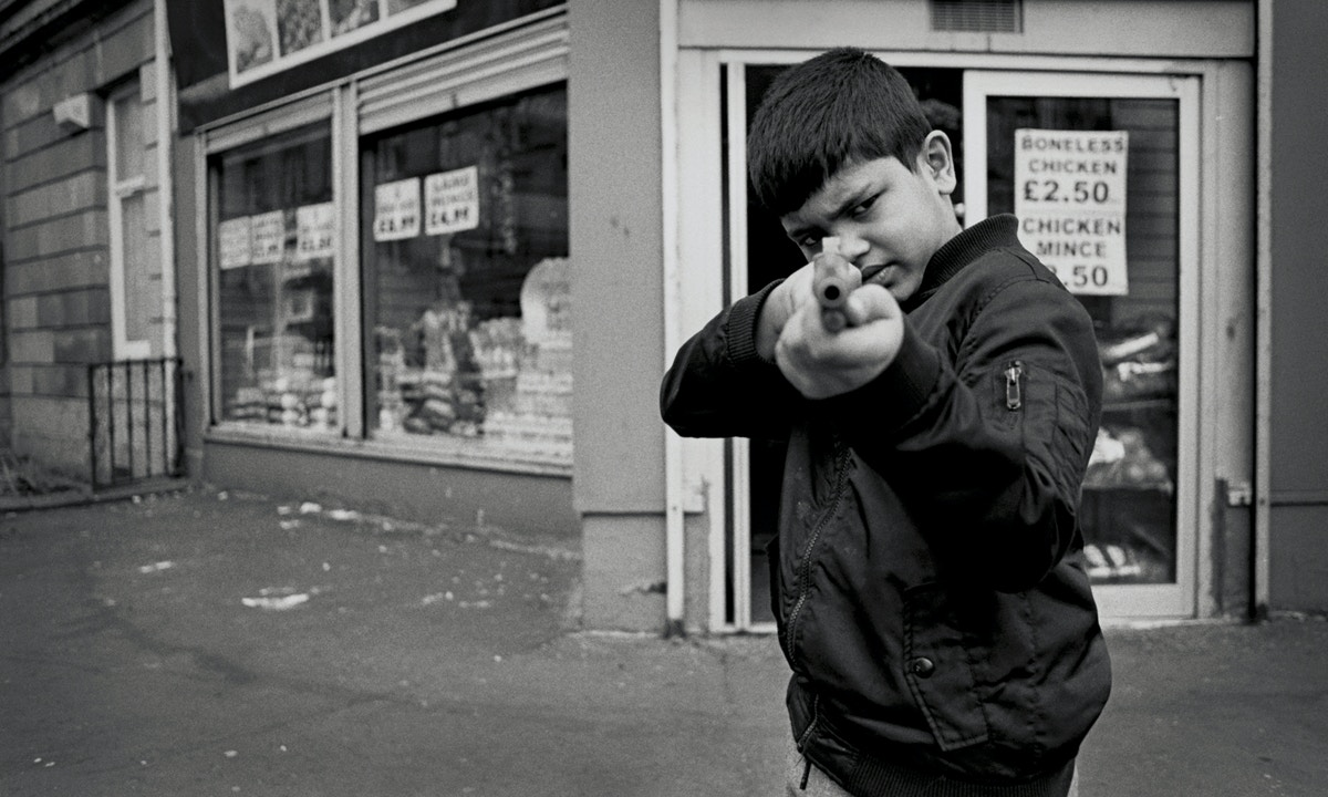 A boy stands in front of a shop pointing a shotgun at the camera. He is wearing a black jacket.