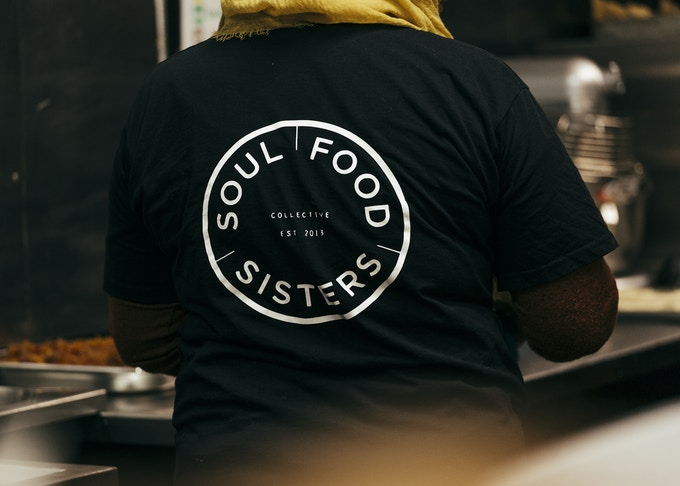 A back print of the Soul Food Sisters logo on a black t-shirt