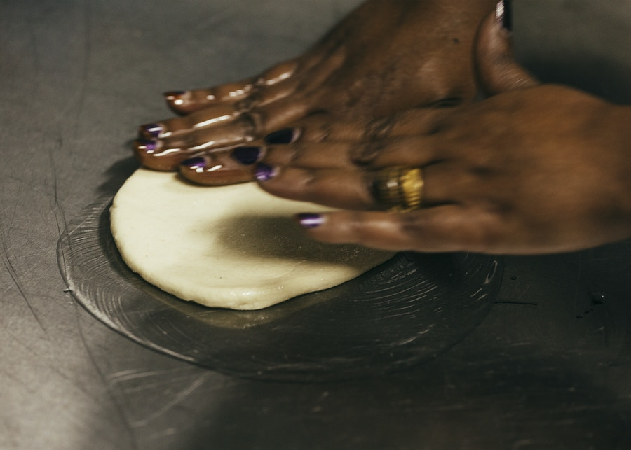 Two hands rolling out dough