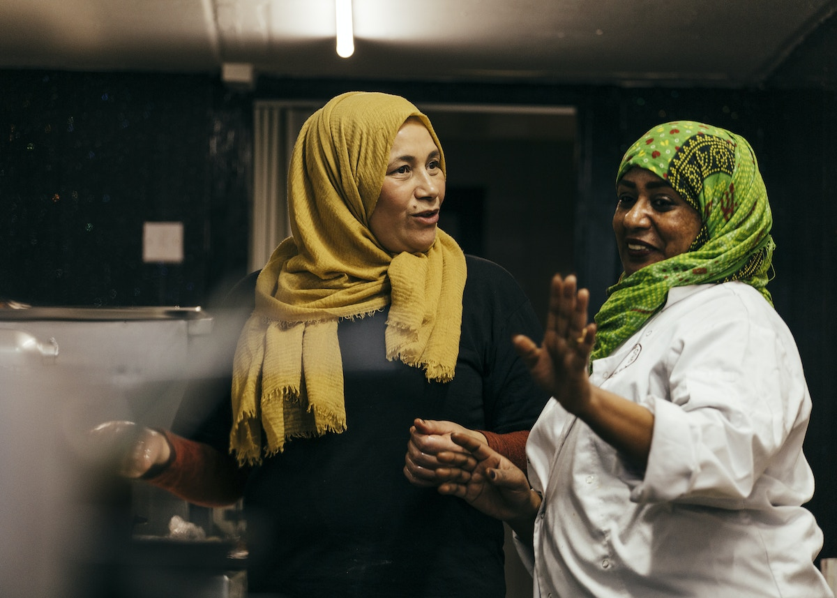 Two women in a kitchen talking together